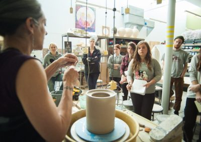 Students watch a wheel throwing demonstration by a visiting artist in a Ceramics class at the Art Lofts.