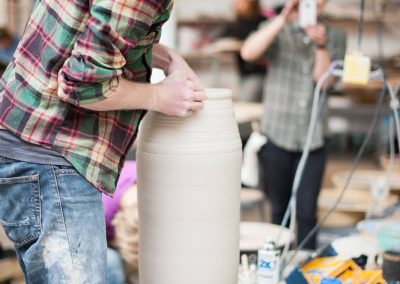 A student snaps pictures of Ben Skiba's technique throwing a tall pot in the Ceramics Lab at the Art Lofts.
