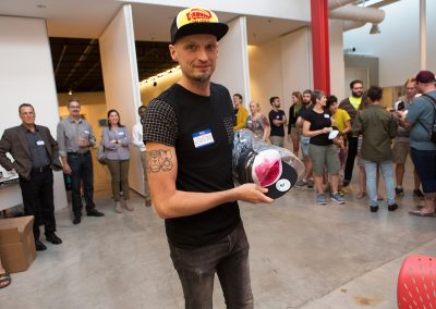 Graduate student Justin Eccles passes out customized trucker hats at the Art Department new graduate orientation event at the Art Lofts Building at the University of Wisconsin-Madison.