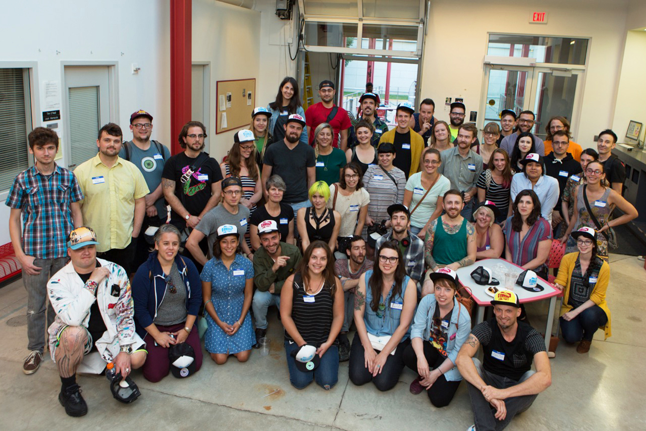 Graduate students pose with custom hats at the at the Art Department new graduate orientation event at the Art Lofts Building at the University of Wisconsin-Madison.