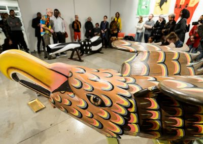 An eagle-shaped coffin fills the foreground as Eric Adjetey Anang, Ghanaian woodcarver, master-coffin builder and Windgate Artist in Residence in the Art Department, speaks during an opening exhibit of Adjetey Anang's work at the Arts Loft at the University of Wisconsin-Madison. During the event, Adjetey Anang led a gun-breaking ceremony and invited guests to participate in a symbolic breaking of the barrel of his gun-shaped coffin. The gun-breaking action was in support of the Black Lives Matter movement, and against gun violence locally, nationally and internationally.