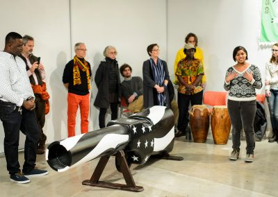 At left, Eric Adjetey Anang (standing at left), Ghanaian woodcarver, master-coffin builder and Windgate Artist in Residence in the Art Department, listens to undergraduate Jamie Dawson, a first-year student in the ninth cohort of the First Wave program, perform a spoken-word piece as part of an opening exhibit of Adjetey Anang's work at the Arts Loft at the University of Wisconsin-Madison. During the event, Adjetey Anang led a gun-breaking ceremony and invited guests to participate in a symbolic breaking of the barrel of his gun-shaped coffin. The gun-breaking action was in support of the Black Lives Matter movement, and against gun violence locally, nationally and internationally.