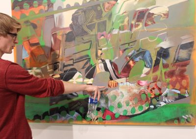 A student critiques a painting at the Art Lofts.