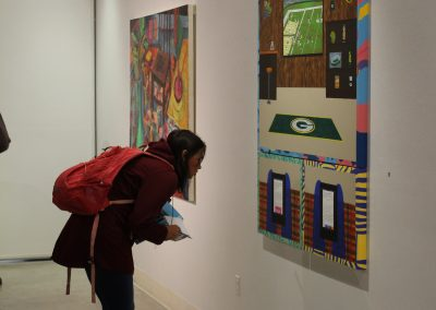 A student examines the writing on a painting at the First Year Grad Show, Witnesses, on display at the Art Lofts Gallery.