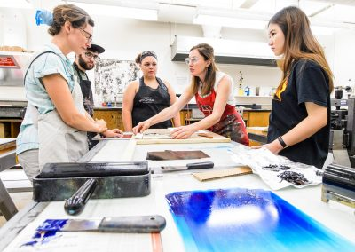 Students work in the printmaking labs in Mosse Humanities Building at the University of Wisconsin-Madison during assistant professor Emily Arthur's (in red apron) Relief Printing course.