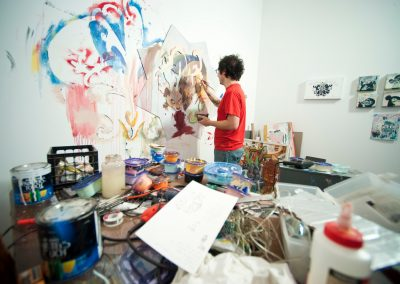 Graduate art student Eddie Villanueva works on a painting in his studio space in the Art Lofts building at the University of Wisconsin-Madison.