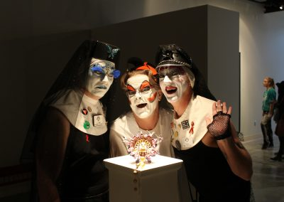 """Drag performers pose with a metals piece by Matt Mauk at his Master of Arts Exhibition """"Hothouse,"""" Art Lofts Gallery, Department of Art University of Wisconsin-Madison"""
