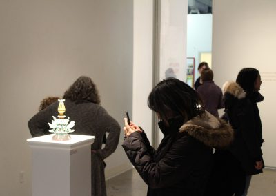 """A visitor photographs a metals piece by Matt Mauk at his Master of Arts Exhibition """"Hothouse,"""" Art Lofts Gallery, Department of Art University of Wisconsin-Madison"""