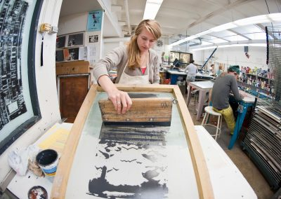 Undergraduate Sigrid Hubertz uses a squeegee to make a printed image in a water-based screen-printing class in the George Mosse Humanities building at the University of Wisconsin-Madison.