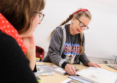 Lynda Barry reviews the work of one of her students, lecturer Allison Welch, at left, in the Making Comics class at the Mosse Humanities Building at the University of Wisconsin-Madison.