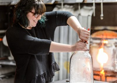 Suzy Peterson explodes a glass Prince Rupert's Drop in a bell jar over a snowflake template during a UW-Madison Glass Lab event in the Art Lofts Building at the University of Wisconsin-Madison.