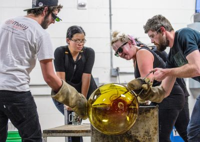 Students work together with an assortment of tools and blown air to shape a piece of molten glass and form Madison''s largest glass ornament during a UW Glass Lab event in the Art Lofts Building at the University of Wisconsin-Madison. The public event featured students performing a number of interesting glass experiments and working together to create a giant Christmas ornament that was auctioned off for charity.