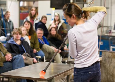 Glass artist Yuki Wakamiya works with an assortment of tools and blown air to shape a piece of molten glass during a demonstration at the Glass Lab open house at University of Wisconsin-Madison.