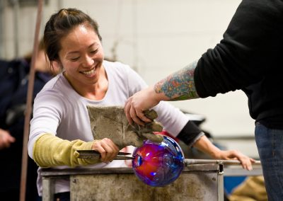Glass artists Quincy Neri (right) and Yuki Wakamiya (left) work together with an assortment of tools and blown air to shape a piece of molten glass during a demonstration at the Glass Lab open house at University of Wisconsin-Madison.