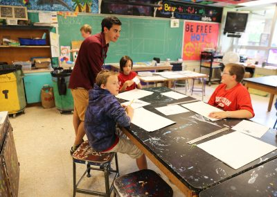 An art education student practices hands-on learning teaching a youth art class. Art education students experience a four semester sequence of classes introducing students to the teaching profession, including child development, learning theories, inclusive schooling strategies, curriculum and instruction, history of American education, and rigorous Art Education methods courses, plus 200 hours of practicum and 18 weeks of student teaching.