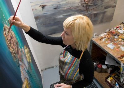 Katelyn Alain, a graduate student pursuing a master of fine arts degree in painting, works on a self portrait in her studio space in the Mosse Humanities Building at the University of Wisconsin-Madison.