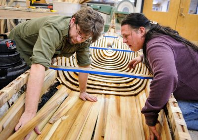 Tim Frandy (at left wearing green shirt), an outreach specialist at the UW Collaborative Center for Health Equity, helps, Wayne Valliere, (at right with ponytail) a Native American artist-in-residence with the Department of Art and member of the Lac du Flambeau Band of Lake Superior Chippewa Indians, install cedar wood slats and steam-bent ribs as Valliere constructs a traditional Ojibwe birchbark canoe at the Mosse Humanities Building at the University of Wisconsin-Madison.
