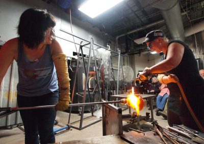 Students use a torch to heat a glass piece at the UW Glass Lab in the Art Lofts Building at the University of Wisconsin-Madison.