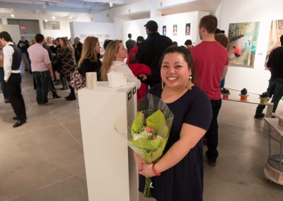 Maixia Xiong poses with her artwork at the BFA Show Reception, Gallery 7 at the University of Wisconsin-Madison