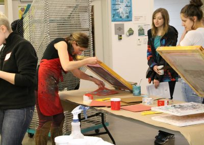 Faculty Emily Arthur demonstrates the serigraphy process.