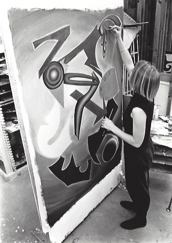 A student works on a large painting.