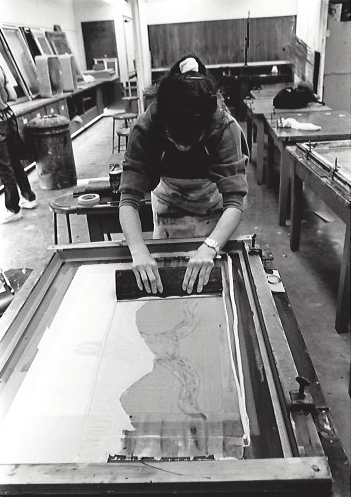 A student squeegees ink along a screenprint.