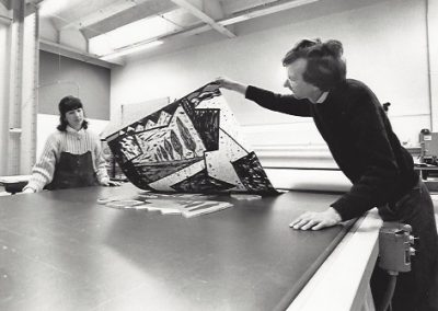A professor removes a block print from a press with a student watching.