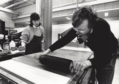 A professor demonstrates rolling out ink on a large plate for printing while a student watches.