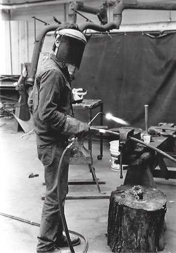A student welds parts of a sculpture.