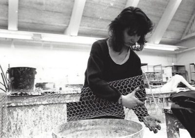 A student uses chicken wire as the base for a sculpture.