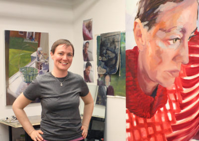 Graduate art student Noel Ash poses with her paintings in her studio space in the Art Lofts building at the University of Wisconsin-Madison.