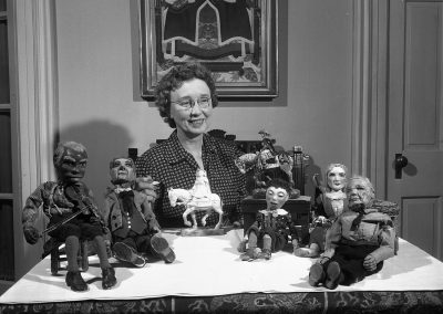 Della Wilson, professor of art from 1915 to 1953, poses with her collection of dolls.
