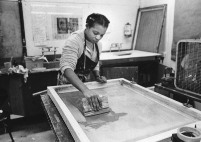 An art student works on a printmaking serigraphy project.