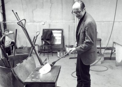Professor of glass Harvey Littleton sculpts molten glass on the end of a blowpipe against a flat surface during a glassblowing demonstration in the hot glass studio. During the 1963 academic year, Littleton introduced the first university program for glass in the United States at the University of Wisconsin-Madison.