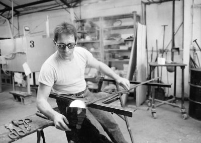 In the hot glass lab, art student Rick Findora uses a block to shape and cool molten glass on the end of a blowpipe in the November of 1985. Findora graduated with a BFA in 1986.