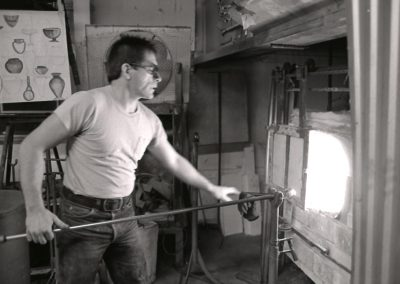 In the November of 1985, art student Rick Findora reheats molten glass on the end of a blowpipe in the glory hole furnace in the hot glass lab. Findora graduated with a BFA in 1986.
