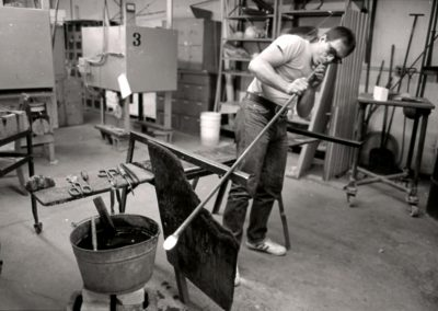 In the hot glass lab, art student Rick Findora blows air into the blowpipe to create a bubble in the molten glass on the end in the November of 1985. Findora graduated with a BFA in 1986.