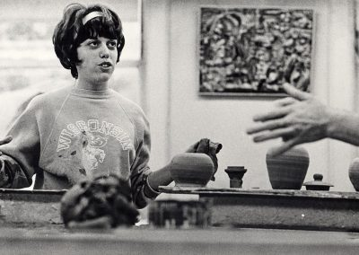 An art student in a Wisconsin Bucky sweatshirt works with clay at a pottery wheel, ca. 1965.