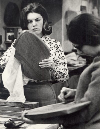 An art student works to finish a piece of carved wood in the 1960s.