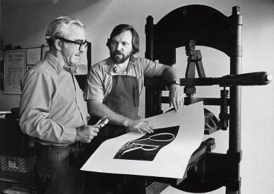 Donald Anderson (left) and Phil Hamilton, both professors of art, look at a print at a press, ca. 1973.