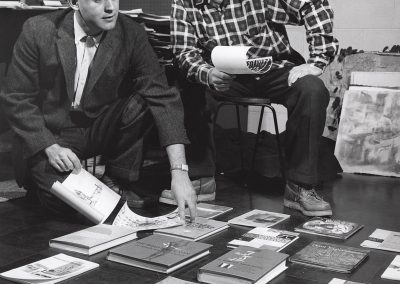 Professor of art from 1947 to 1982 Donald M. Anderson (right) and Bill H. Armstrong, an assistant professor in the department of art education from 1955 to 1963, look over books spread out on the floor.