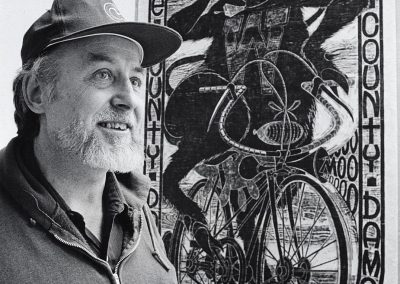 "Ray Gloeckler, professor of art, poses in from of his woodcut, ""Dane County Damsel,"" ca. 1985."