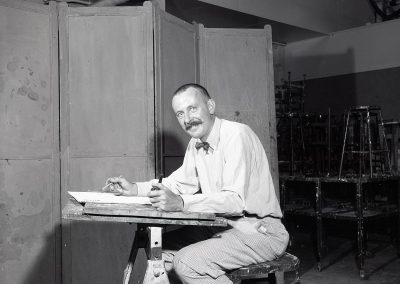 Professor John Wilde poses at a drafting table in September of 1960. Wilde was associated with the Magic Realism movement and Surrealism in the United States. His darkly humorous figurative imagery often included self-portraits through which he interacted with the people, animals and surreal objects that populated his fantasy world.