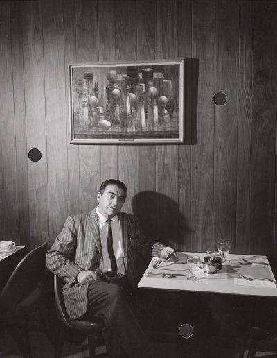 "Professor Santos Zingale poses with his painting ""Still Life"" at the Memorial Union, ca. 1962."
