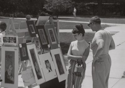 Pedestrians browse art for sale at the 1964 Library Mall Art Fair.