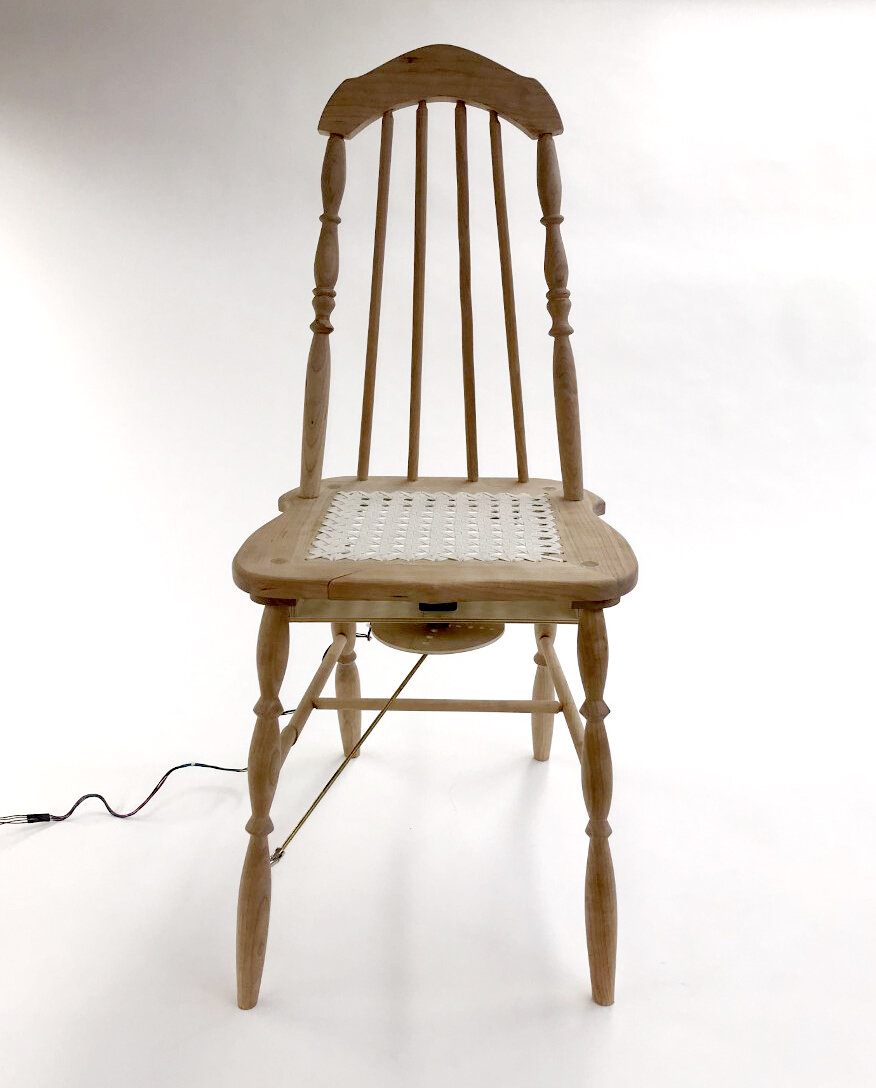 Miss Manners, animatronic wicker chair furniture sculpture by Stacy Lynne Motte which extends one leg in a bow when someone approaches.