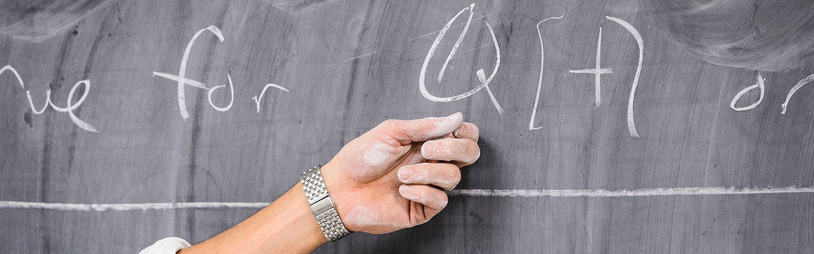 Chalky hand pointing to mathematical equation on blackboard