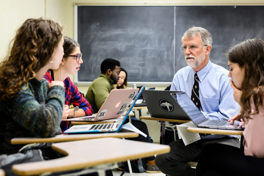 Students engaged in discussion with professor in a classroom
