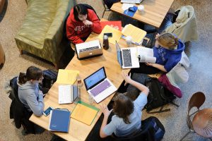 Overhead shot of people studying collabratively on laptops