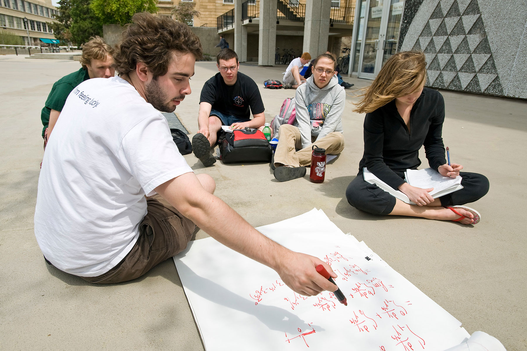 Students studying math on the sidewalk